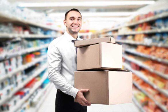 Homem no supermercado segurando uma caixa de papelão